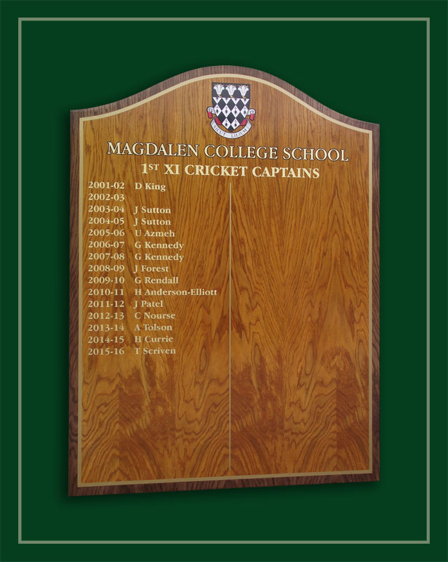 An oak veneered honours board listing the cricket captains of Magdalen College School