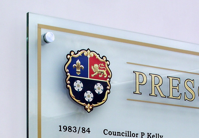 Close up of perspex honours board showing a printed Prescot town council crest.