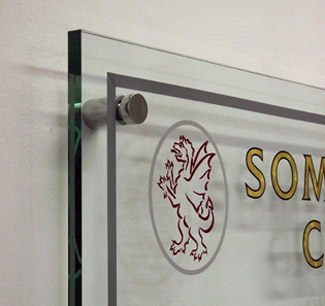 A closer view of the Somerset Cricket Club logo displayed on glass effect panel
