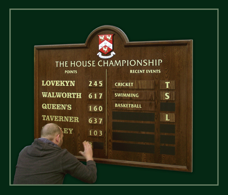 Magnetic panels being fixed to a school house championship board